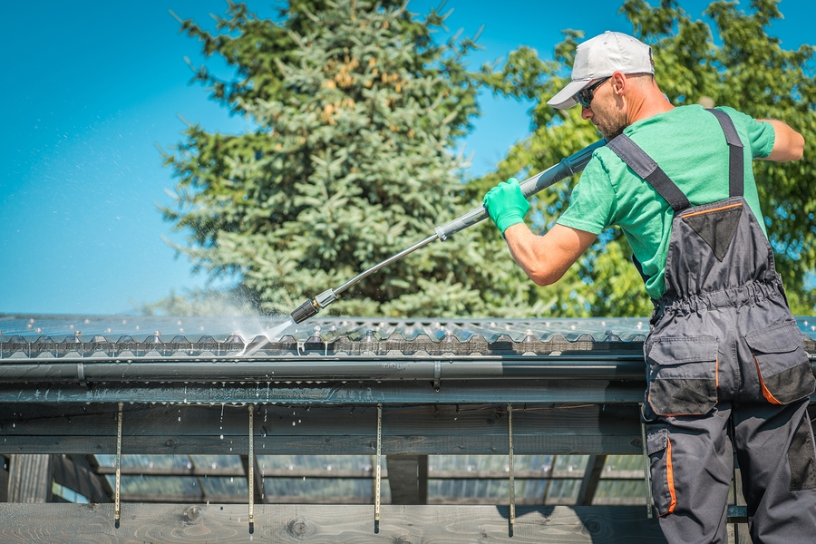 Roof And Gutters Power Cleaning Using Pressure Washer. Caucasian